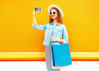 Fashion young smiling woman takes a picture self portrait on the smartphone on a orange background