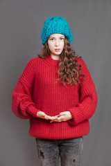 A girl in a red woolen sweater and a blue winter hat posing in the studio on a gray background.