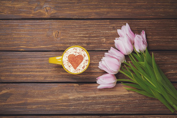 Cup of coffee cappuccino with spring tulips