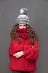 The girl wore a large red woolen scarf and sweater. The head is bright. Studio gray background.