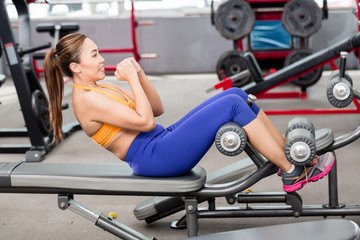 Sportive Asian woman doing sit-ups on bench in fitness club wearing crop top
