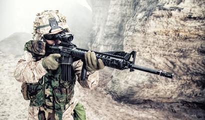 US Marine Corps Soldier in action among the rocks