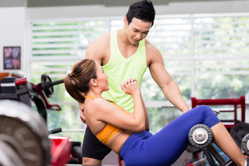 Sportive male instructor advising Asian woman doing sit-ups on bench in gym
