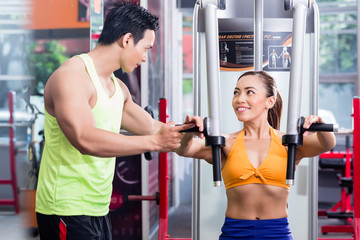 Instructor supervising sportive woman during machine workout at butterfly station in fitness center