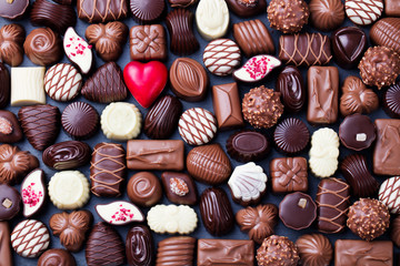 Assortment of fine chocolate candies, white, dark, and milk chocolate Sweets background. Copy space. Top view.