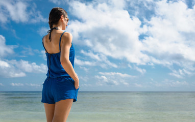 Woman Tourist in sundress at the sea looking to horizon