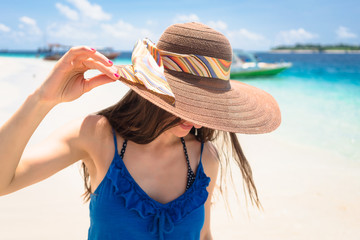 Woman wearing sun hat at beach by the ocean relaxing in her vacation