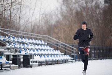 Image of running athlete in black clothes at stadium