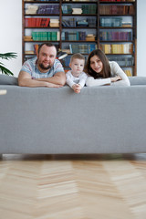 Image of happy woman and man with boys on gray sofa