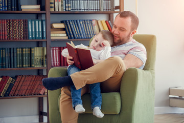 Picture of daddy reading book to son sitting in chair