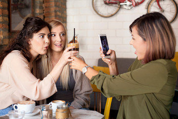 Three female friends making a toast with coffee. Women at cafe, talking, laughing and enjoying their time. One woman making a picture of other two.