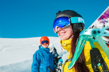 Photo of sporty couple with snowboard against background of snowy hills