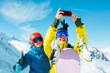 Picture of sports man and woman in helmet making selfie against background of snowy hills