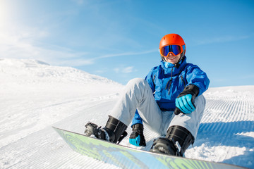 Photo of sports man wearing blue jacket, helmet with snowboard sitting on snowy slope