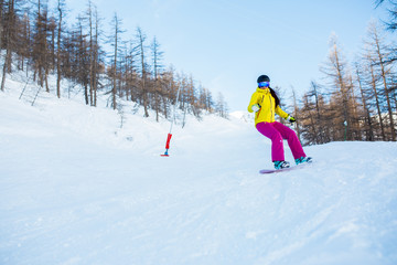 Picture of athlete woman wearing helmet and mask snowboarding from snowy slope with trees