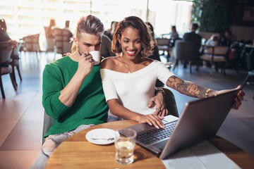 Young interracial lovers spending time in cafe watching media together on laptop