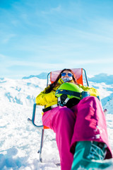 Pictures of sporty woman with helmet resting on chair in winter resort