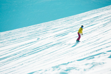 Image of sports girl wearing helmet and mask snowboarding from mountain slope