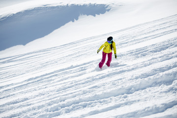 Picture of brunette wearing helmet and mask in sports clothes, snowboarding from snowy mountain slope