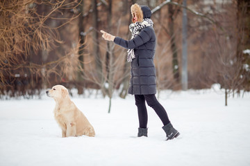 Picture of girl in black jacket training dog in snowy park