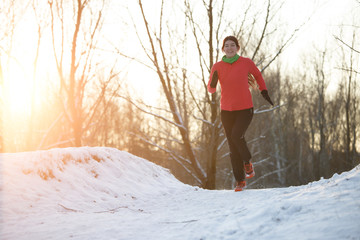 Picture of sports woman on run through winter forest
