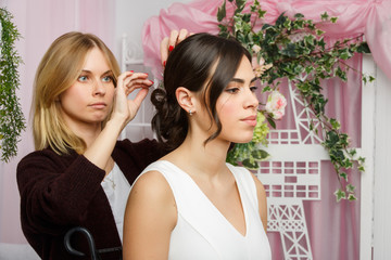 Image of girl and stylist adjusting hair in pink studio