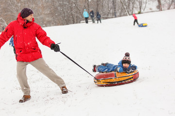 Image of man rolling his son on winter day