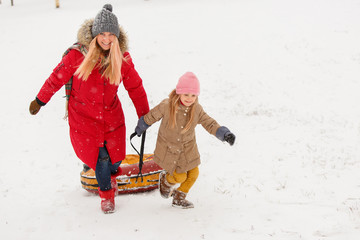 Photo of mother and daughter on walk with tubing in winter park