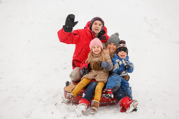 Photo of happy parents with daughter and son sitting on tubing in winter