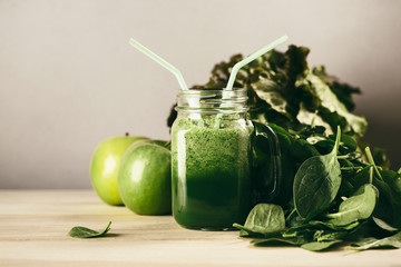 Green detox juice jar with green vegetables with two straws.