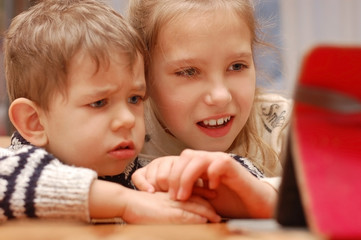 A cute young girl and her younger brother are sitting at the table and looking at the cartoon tablet with enthusiasm