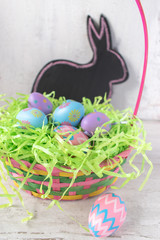 Easter basket with colorful eggs with chalkboard bunny shape in background