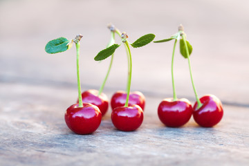 Red cherries berry with green leaves. Ripe fruit macro view photo. Selective focus, shallow depth of field. Beautiful bokeh background.