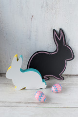 chalkboard bunny shape with wood cut out bunny on white background with pink and purple pattered eggs