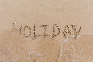 Holiday character on the sand is being washed away. The time of rest is about to expire and ready to start to work.
