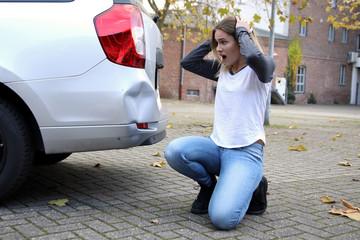 Hübsche blonde Frau kniet vor einem beschädigten Auto und ist entsetzt