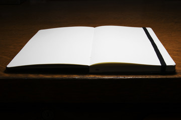 Open book on an office desk. Blank Slate. Time to start working. Personal diary.