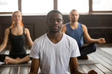 Young black man and a group of sporty people practicing yoga lesson with instructor, sitting in Sukhasana exercise, Easy Seat pose with mudra gesture, students training in club, working out, close up Wall mural