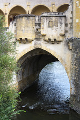 One arch of an old french bridge over the river in the summer day