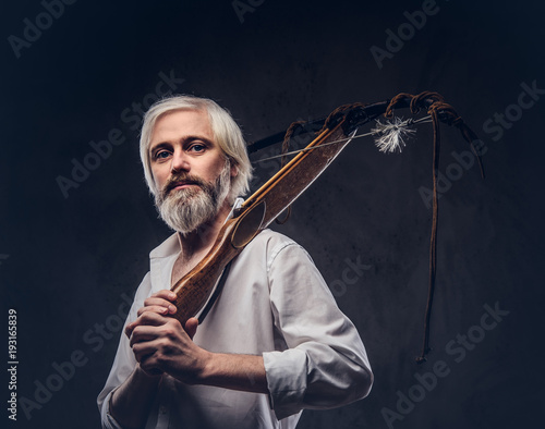 7e379f5416a Studio portrait of a smiling handsome old man with a gray beard and white  shirt holding a crossbow on shoulder.