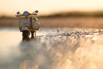 Modell Motorroller vor romantischem Sonnenuntergang mit Lensflares