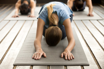 Yogi woman and a group of young sporty people practicing yoga lesson with instructor, stretching in Child, exercise, Balasana pose, working out, indoor, studio, close up. Healthy lifestyle concept