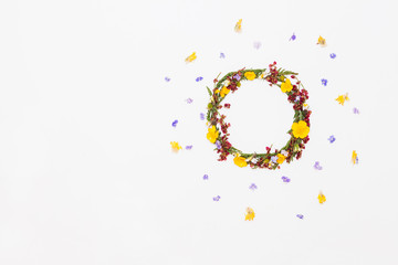 Wreath from summer field flowers on white background with violet and yellow flowers around