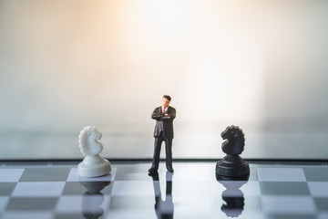 Business and Competition Concept. Businessman miniature figure standing on chessboard with black and white knight chess pieces