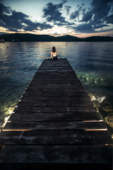 Woman sitting at the pier and enjoying the sea view. Beautiful sunset at the Croatia. Wooden pier with backlight.