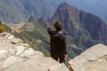Man looking at Machu Picchu from Sun Gate, Peru