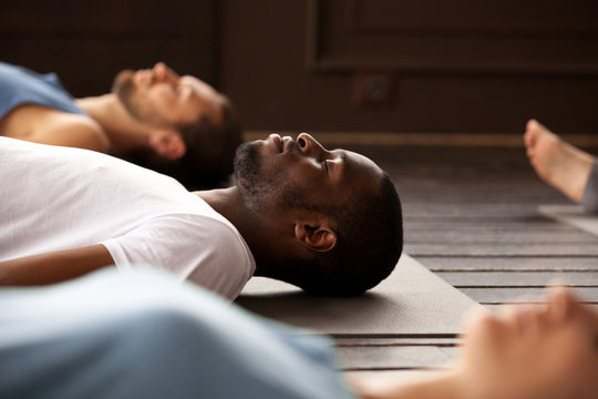 Group of young afro american and caucasian sporty people practicing yoga lesson lying in Dead Body or Corpse pose, Savasana exercise, resting after practice, working out, indoor close up, studio