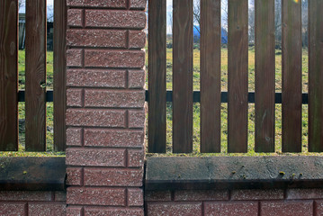 Fence of wooden rails and bricks