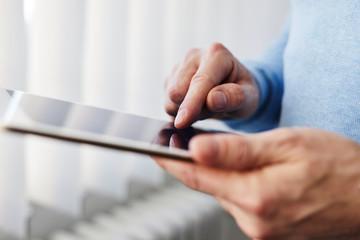 Man working on a digital tablet near a window