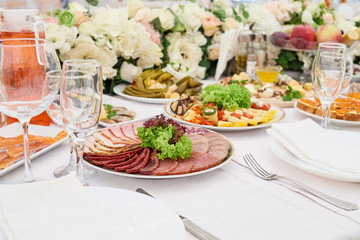 Cold meat plate on celebratory dinner table, copy space. Meat platter with selection on wedding banquet